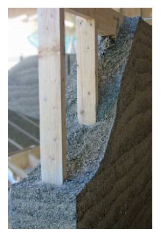 Hemp mixed with lime, aka hempcrete, is not concrete and thus needs structural support. It's main use is insulation and air sealing. In this photo it is stick frame. In the future we suspect somebody will find a way to make it structural. A skilled green builder could use this for NY extensions as well as insulating existing brick structures.